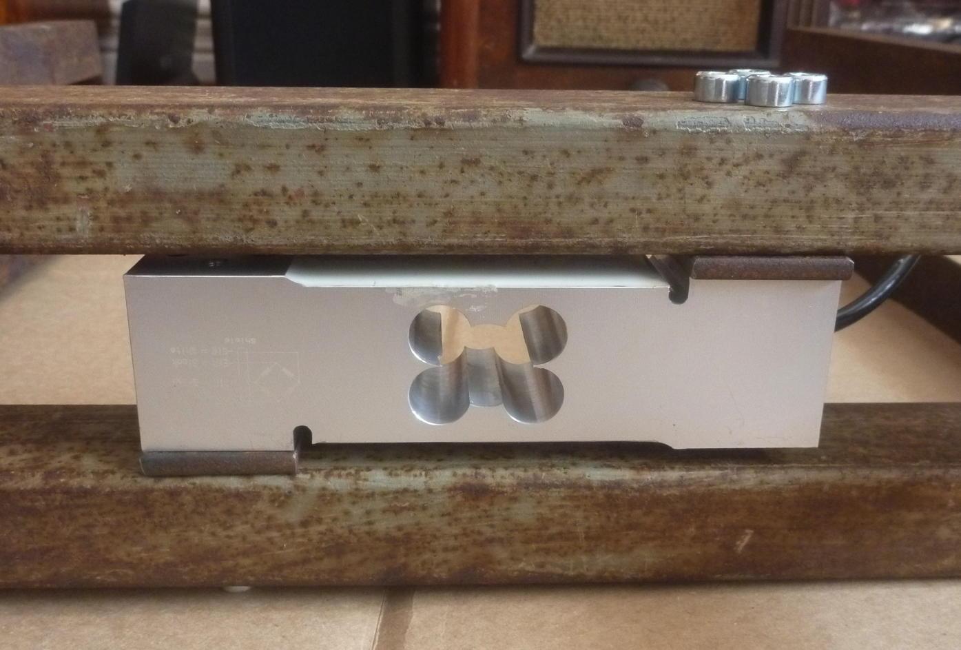 Wägezelle verschraubt zwischen den zwei H-Stücken des Wiegegestells